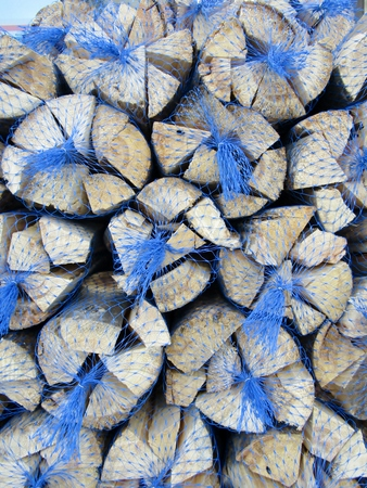 Kiln dried logs in netted bags Imagens