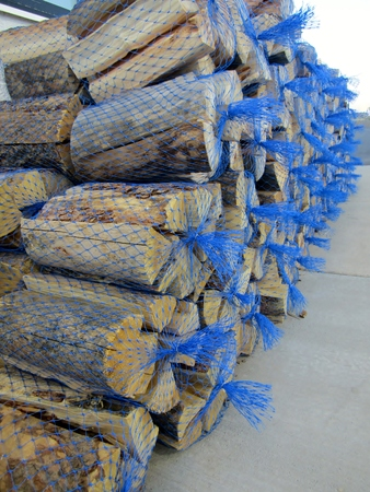 Stack of kiln dried logs in net bags