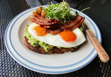 Mashed avocado on whole grain bread toast with sunny side egg topped with bacon, roasted baby potatoes and curly endive lettuce Stock fotó