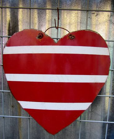 Metal heart with red and white stripes as a rustic garden decor