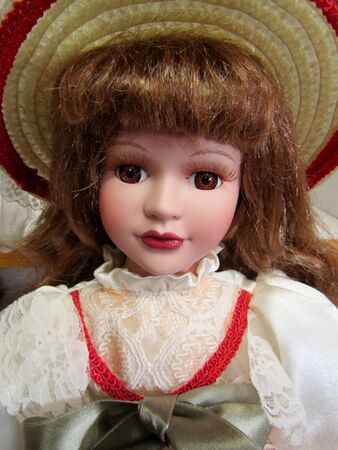 Porcelain doll in straw hat close up