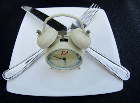 Twin bell alarm clock with white plate, fork and knife as fasting concept Stock fotó