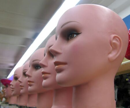 Row of mannequin heads on shelf