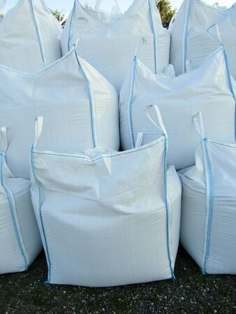 Stack of white large canvas bags with gravel