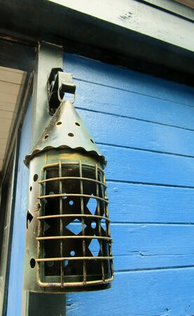 Antique metal candlelight hanging on blue wooden wall Stock fotó