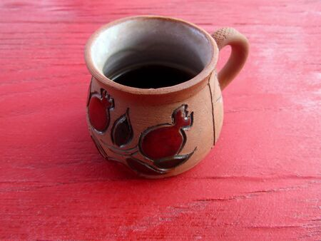 Black coffee in clay cup on red patio table