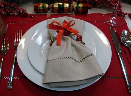 Festive napkin, jingle bells and cracker on the Christmas table