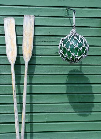 Boat wooden paddles and buoy against a green wall