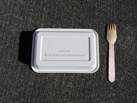 Disposable bio corn starch tray and wooden fork on concrete background Stock fotó