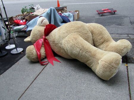 Moving out: large toy bear and other belongings lying on the street.