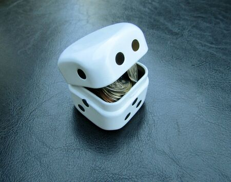 Container in shape of gambling dice full of coins