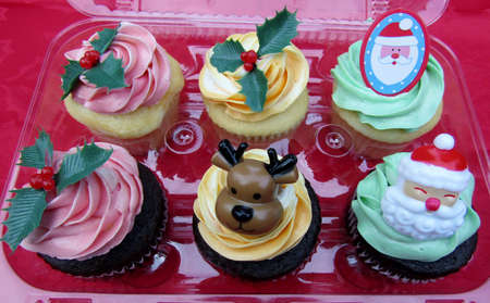 Christmas festive cupcakes with colorful cream frosting decorated with small plastic toys