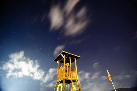 convective: Lifeguard watch tower by the sea and the night sky stars