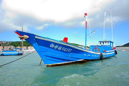 Blue fishing boats docked at black rock pond in zhoushan, zhejiang province Editorial