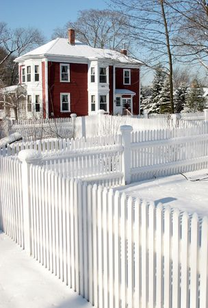 Red house behind a white fence under snow photo