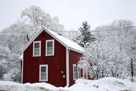 casa colonial: Rojo casa entre los �rboles bajo la nieve Foto de archivo
