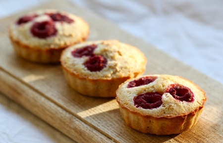 Three raspberry muffins on a wooden board close up
