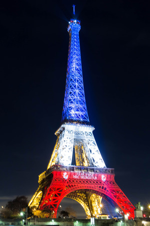 Eiffel Tower: Pris, France, November 18, 2015: The Eiffel Tower lit up with the colors Of the French national flag Blue, White and Redto honor victims of the November 13 terrorist attacks in Fridays Paris.