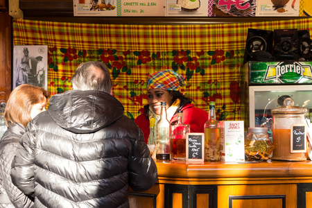 salesgirl: Paris; France-November 22; 2015: The unidentified salesgirl  selling West Indies food  at Christmas market on Champs Elysees avenue in Paris, France. Editorial