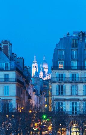 The Sacre-Coeur basilica seen between two Haussman-style buildings, Paris, France.