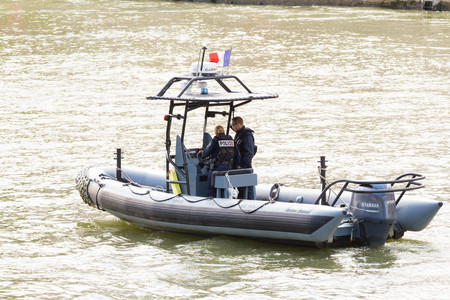 Paris; France-July 14, 2016 : The Police boat is patrolling on the Seine river near Notre Dame cathedral in Paris, France.