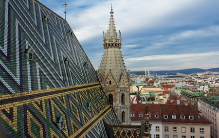 innere: Aerial view over the rooftops of Vienna from the north tower of St. Stephens Cathedral including the cathedrals famous ornately patterned, multi colored roof created by 230,000 glazed tiles, Austria