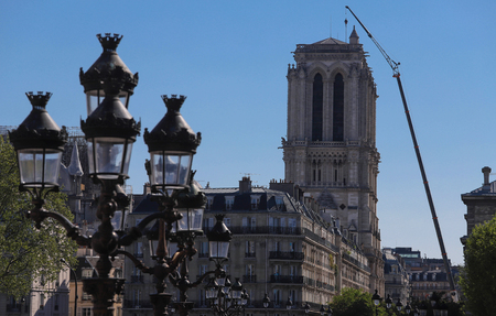 The towers of Notre Dame cathedral ater fire with giant crane near. The lamp posts of Hotel de ville square in the foreground. Paris.