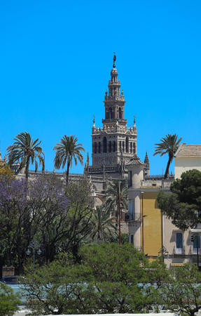 Famous tower of Giralda, Islamic architecture built by the Almohads and crowned by a Renaissance bell tower with the statue of Giraldillo at its highest point, Seville Cathedral. Фото со стока