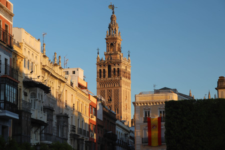 Famous tower of Giralda, Islamic architecture built by the Almohads and crowned by a Renaissance bell tower with the statue of Giraldillo at its highest point, Seville Cathedral. Фото со стока - 124985695