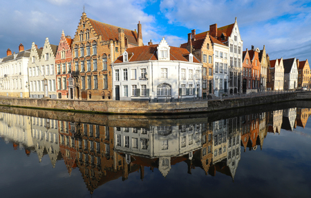 Scenic city view of Bruges canal with beautiful medieval colored houses, bridge and reflections at sunny day.