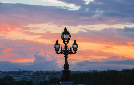 Paris skyline at sunset, with lamp post of Alexandre III bridge, Paris, France Stock Photo