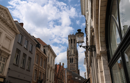 The tower of belfry and traditional buildings with ancient lamp post , Bruges, Belgium Imagens