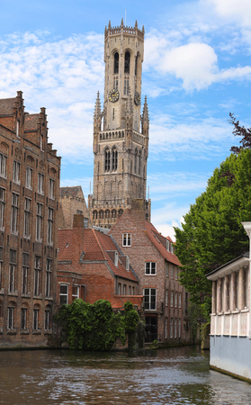 Famous view of Bruges tourist landmark attraction - Rozenhoedkaai canal with Belfry and old houses along canal with tree . Belgium Stok Fotoğraf
