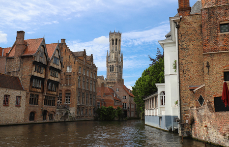 Famous view of Bruges tourist landmark attraction - Rozenhoedkaai canal with Belfry and old houses along canal. Bruges, Belgium Imagens