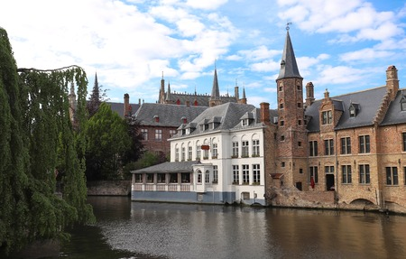 Scenic city view of Bruges canal with beautiful medieval colored houses and reflections.