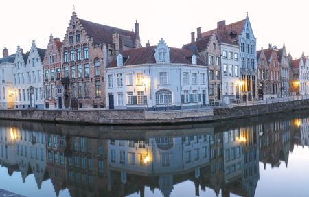 Scenic city view of Bruges canal with beautiful medieval colored houses and reflections in the evening.