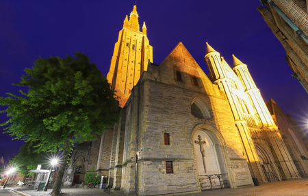 Night view of a typical street of historic Bruges, with Church of Our Lady as background, Belgium
