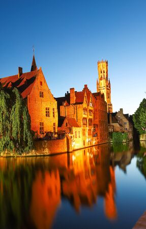 Famous view of Bruges tourist landmark attraction - Rozenhoedkaai canal with Belfry and old houses along canal with tree in the night. Belgium Stok Fotoğraf