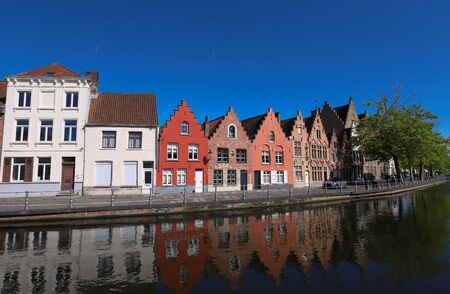 Scenic city view of Bruges canal with beautiful medieval colored houses, bridge and reflections at sunny day, Belgium Imagens