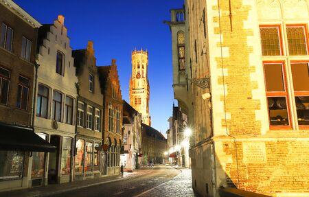 Belfry of Bruges and night street Bruges, Flemish Region, Belgium Фото со стока