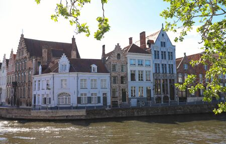 Scenic city view of Bruges canal with beautiful medieval Flemish colored houses .