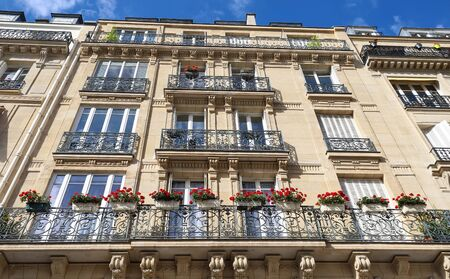 Traditional French house with typical balconies and windows. Paris. Фото со стока