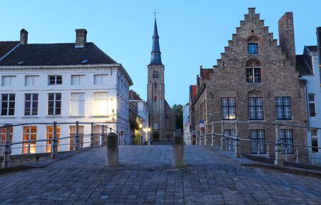 Scenic city view of Bruges with beautiful medieval houses and Saint Anne church in the background in the evening.