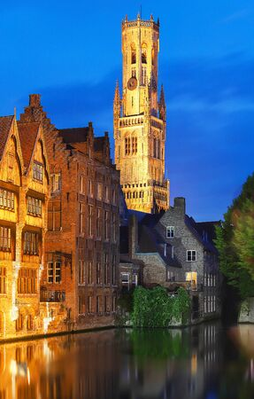 Famous view of Bruges tourist landmark attraction - Rozenhoedkaai canal with Belfry and old houses along canal with tree in the night. Belgium Фото со стока