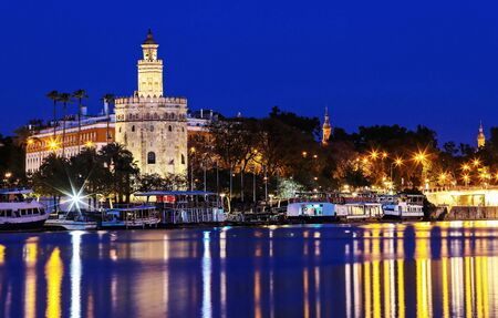 Torre del Oro -Tower of Gold on the bank of the Guadalquivir river at night , Seville, Spain