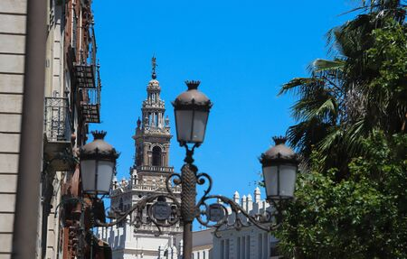 The Giralda is the bell tower of the Cathedral of Seville in Seville, Spain, one of the largest churches in the world and traditional lamp post in the foreground.