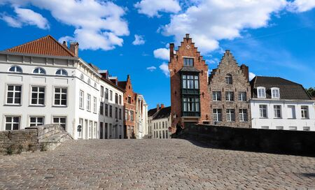 Scenic city view of Bruges canal with beautiful medieval colored houses .