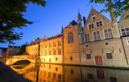 Scenic city view of Bruges canal with beautiful medieval colored houses and reflections, Belgium