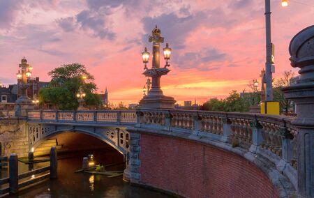 Blauwbrug Blue Bridge over Amstel river in Amsterdam at sunset spring evening, Holland.