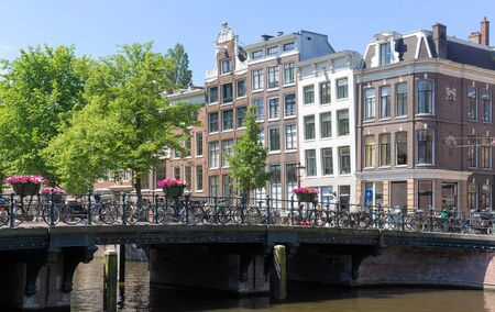 Beautiful view of Amsterdam canals with bridge and typical dutch houses. Holland